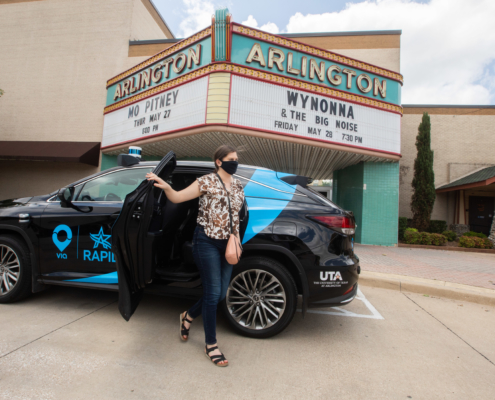 A woman exiting a May Mobility shuttle in front of the Arlington theater in Arlington, TX.